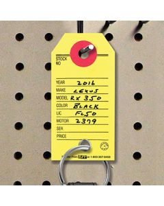 Paper Key Tags with a vehicle key on a pegboard at an auto dealer lot