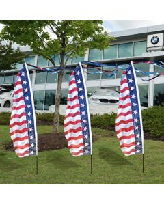 Patriotic Feather Dancer Message Flag Kits on poles in front of an auto dealership