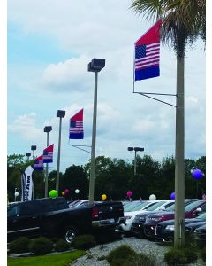Single Sided Motion Bracket Flags on poles at an auto dealership