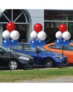 Premium Reusable Balloon Cluster Kit on poles next to vehicles in an auto dealership