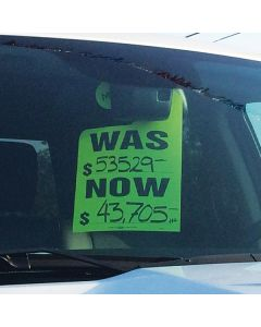 Fluorescent Hang Tag New Style green hanging on mirror in vehicle at an auto dealership