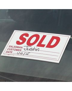 Sold Sticker red on white on vehicle windshield at an auto dealer lot